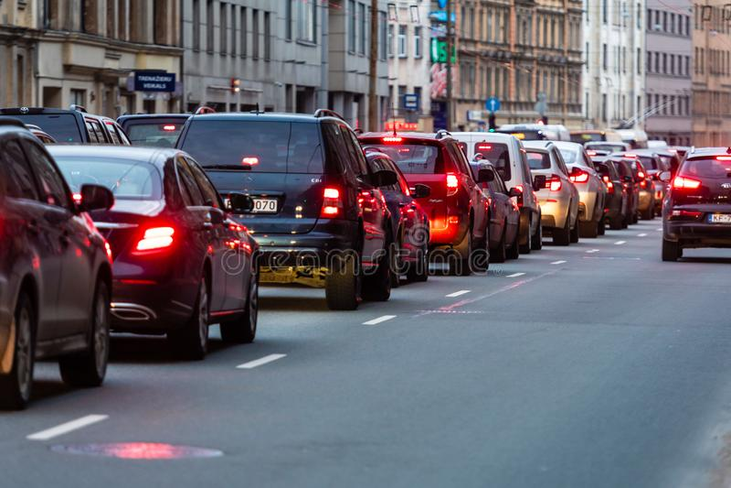 RIGA, LET?NIA - 27 DE MAR?O DE 2019: Engarrafamentos na cidade com fileira dos carros na estrada em luzes da noite e do bokeh - i fotos de stock