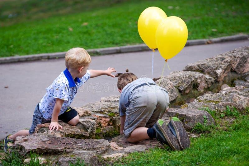 RIGA, LETLAND - AUGUSTUS 18, 2018: Jongen met ballons in van het de stadspark van handenspelen het waterkanalen stock foto's