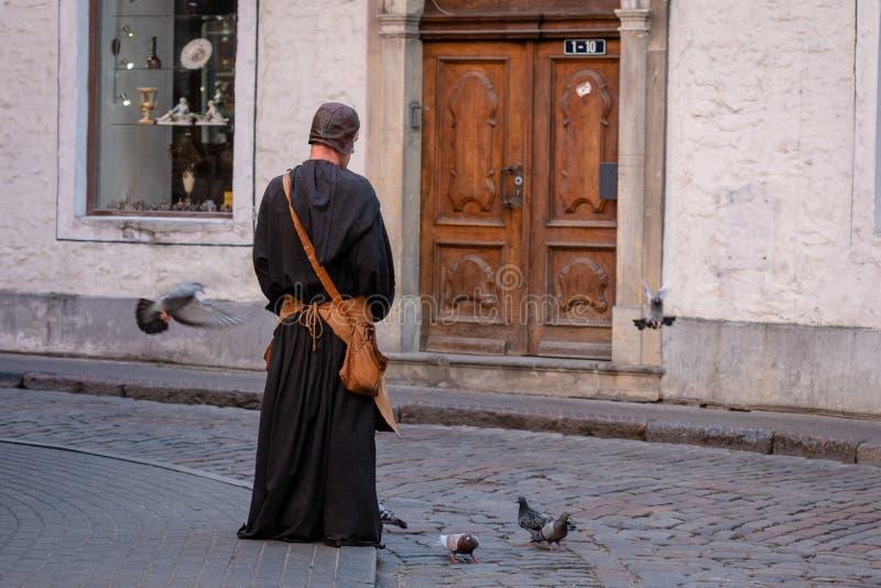 RIGA, LETLAND - JULI 31, 2018: De mens in middeleeuwse kleren in de oude stad op de straat voedt de duiven stock fotografie