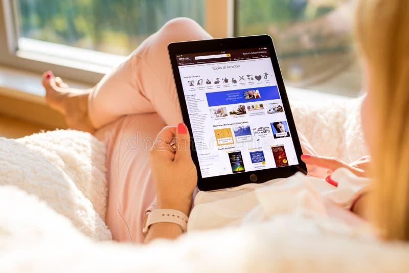 Riga, Letland - Juli 21, 2018: Vrouw die voor boeken op de website van Amazonië op iPad winkelen royalty-vrije stock fotografie