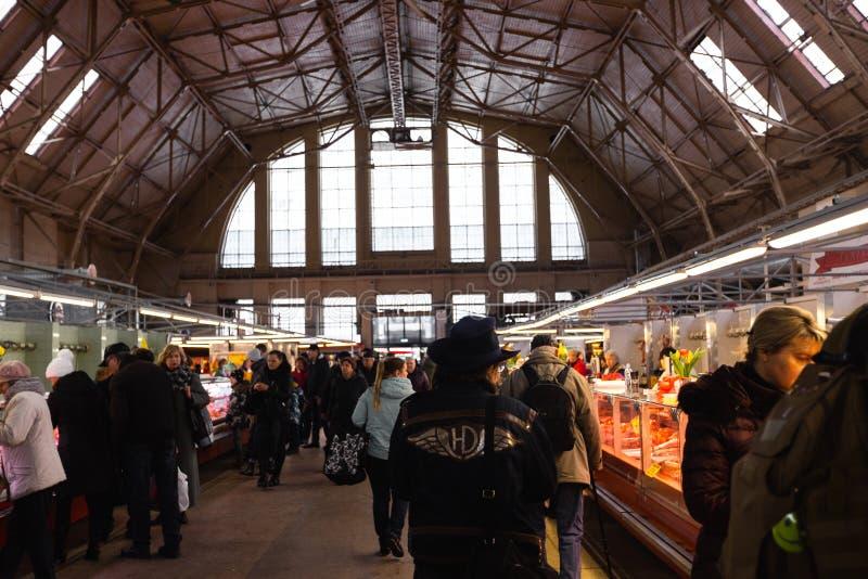 RIGA, LETLAND - MAART 16, 2019: Centraal het marktvleespaviljoen van Riga, mensen die vers voedsel kopen - Vroegere zeppelinhanga royalty-vrije stock foto