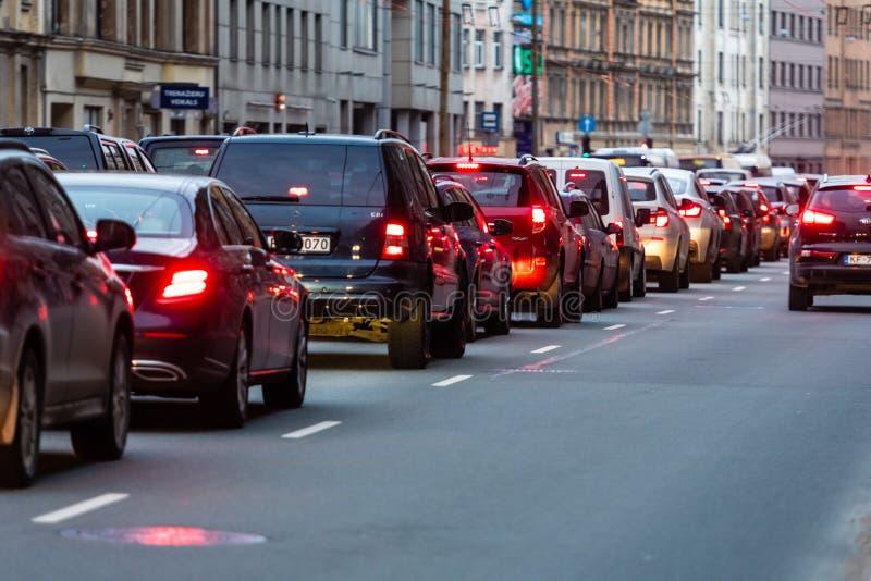 RIGA, LETLAND - MAART 27, 2019: Opstoppingen in de stad met rij van auto's op de weg bij avond en bokeh lichten - beeld stock foto's