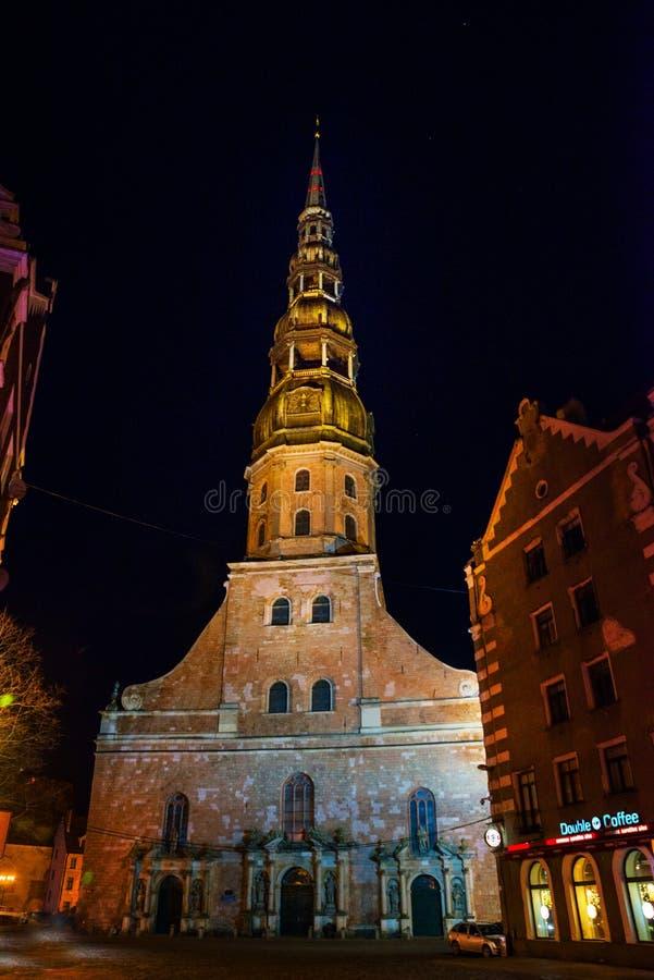 Riga, Letland: Nachtweergeven van St Peter Kerk in Oude Stad Riga Letland Verlichte straat stock foto's
