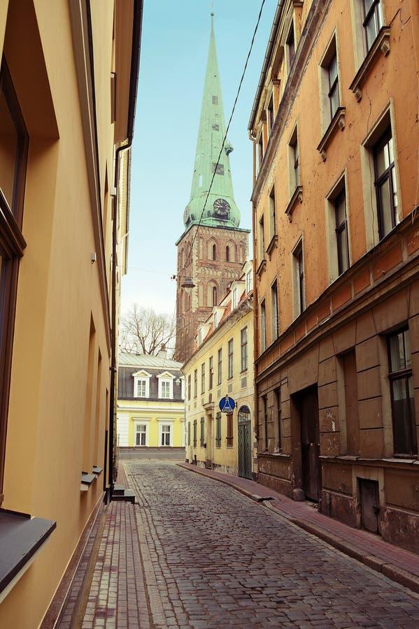 Riga, Letland Smalle middeleeuws cobbled ielastraat van Maza Miesnieku met huurkazernes in de oude stad van Riga stock afbeeldingen