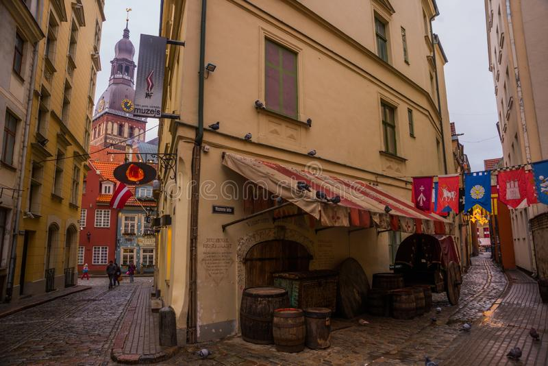 Riga, Letland: Vlaggen die op iela van straatrozena hangen Smalle straat in oude stad Riga Koepelkathedraal op de volgende straat stock foto's