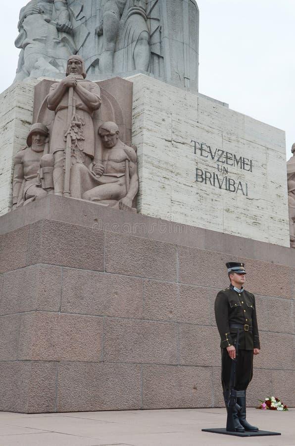 Riga, Letonia - 10 de agosto de 2014 - guardia honorario de Solider hace una pausa el monumento de la libertad bajo día nublado e foto de archivo