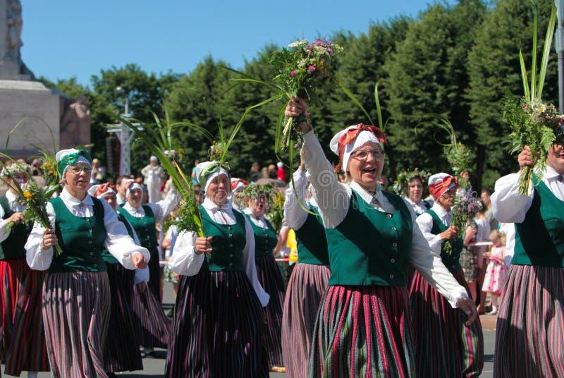 RIGA, LETONIA - 7 DE JULIO: Gente en trajes nacionales en el Latvi imagen de archivo libre de regalías