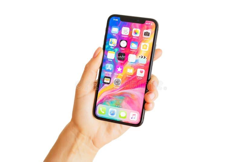 Riga, Letonia - 15 de marzo de 2018: Ciérrese encima de la foto de la última mano del ` s del iPhone X de la generación personalm foto de archivo libre de regalías