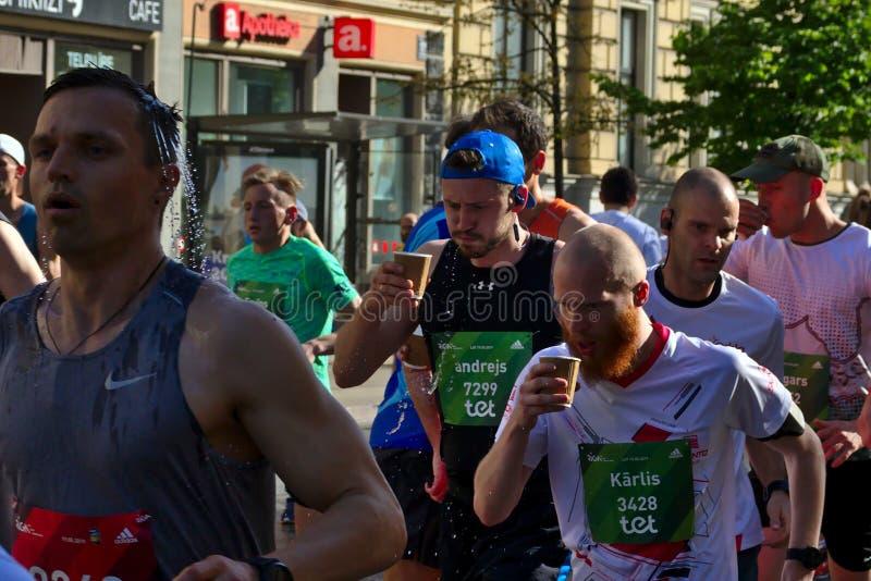 Riga, Letonia - 19 de mayo de 2019: Agua potable de los corredores de marat?n en muchedumbre grande imagen de archivo libre de regalías