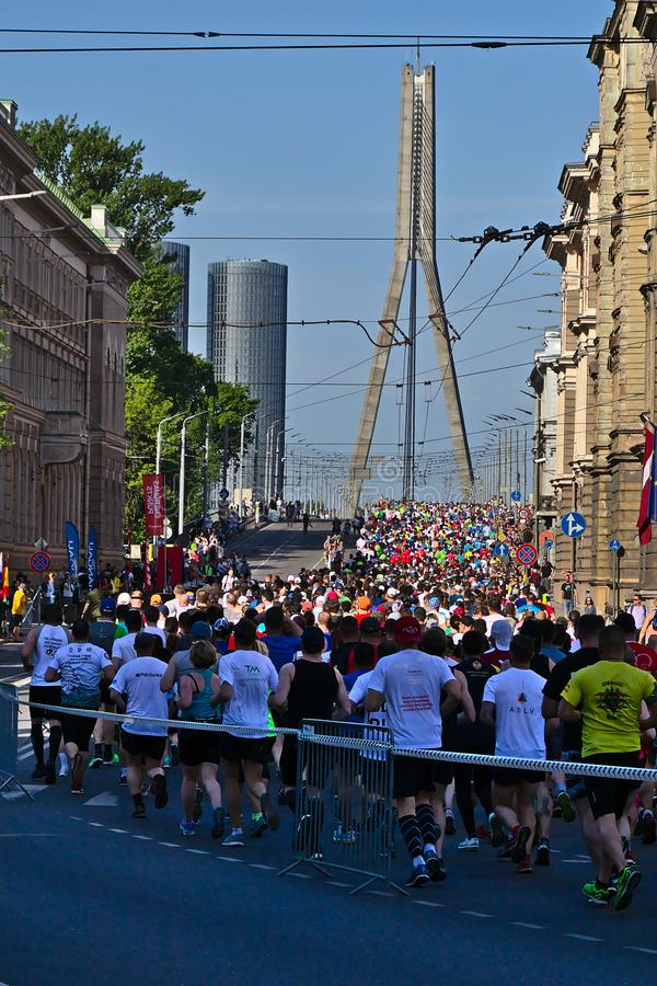 Riga, Letonia - 19 de mayo de 2019: Corredores de marat?n que llegan al puente de Vansu fotos de archivo