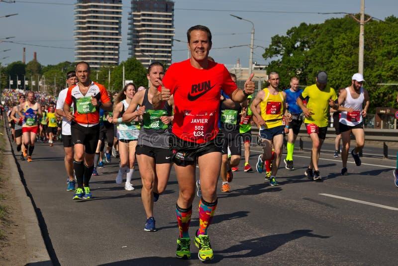 Riga, Letonia - 19 de mayo de 2019: Hombre envejecido medio que contin?a feliz marat?n con ambos pulgares para arriba fotos de archivo libres de regalías