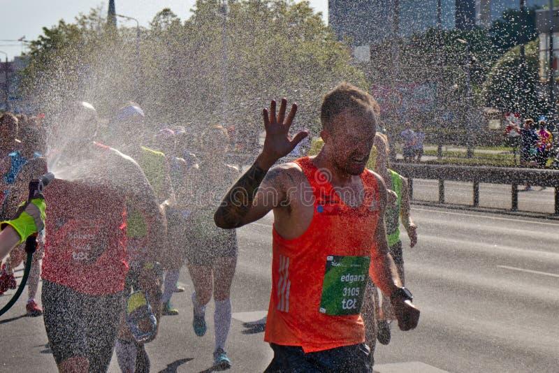 Riga, Letonia - 19 de mayo de 2019: Participante masculino del espray de agua de recepci?n del marat?n a la cara de los hes imagen de archivo