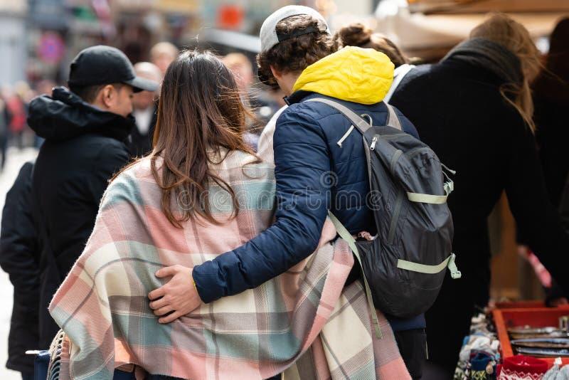 RIGA, LETONIA - 4 DE MAYO DE 2019: Un par de personas abrazadas están caminando abajo de la calle Visi?n trasera fotos de archivo