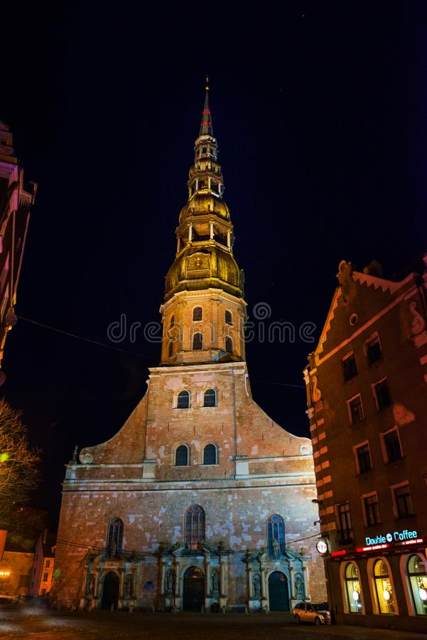 Riga, Letonia: Vista nocturna de la iglesia de San Pedro en la ciudad vieja Riga Letonia Calle iluminada fotos de archivo