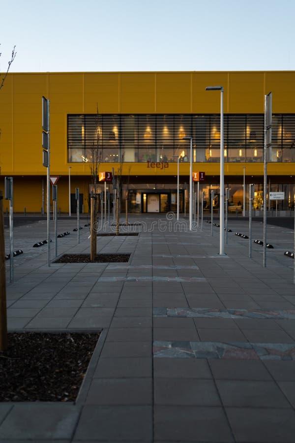 RIGA LETTLAND - APRIL 3, 2019: Huvudsaklig ingång för IKEA galleria under mörk afton och vind - blå himmel i bakgrunden arkivfoto