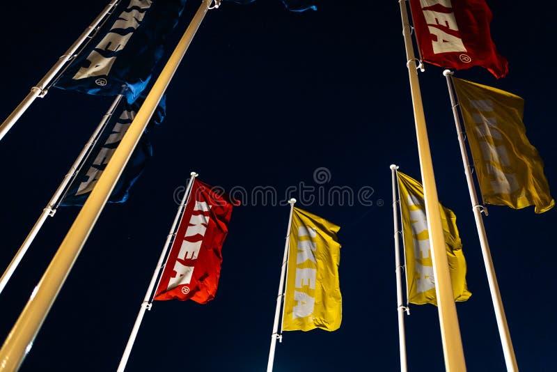 Riga Lettland - April 3, 2019: IKEA flaggor under m?rk afton och vind - bl? himmel i bakgrunden royaltyfria foton