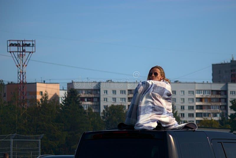Riga Lettland - Augusti 02, 2019 - hållande ögonen på drivakonkurrens för kvinna överst av ett tak arkivbild