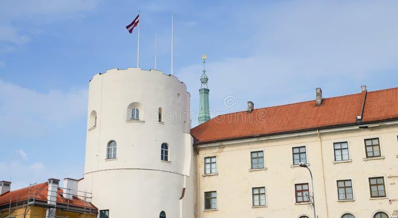 Riga Lettland - Augusti 10, 2014 - Riga caslte med den Lettland flaggan i himlen Slotten är en uppehåll för en president av Lettl arkivbild
