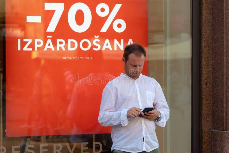 RIGA, LETTLAND - 26. JULI 2018: Ein Mann in einem weißen Hemd und in einem Smartphone steht nahe bei dem Schaufenster lizenzfreies stockbild