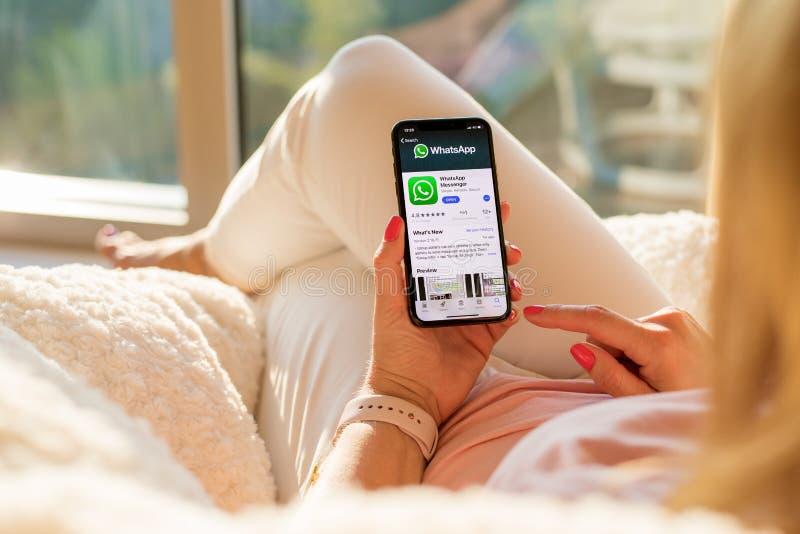 Riga Lettland - Juli 21, 2018: Kvinna som ser WhatsApp på mobiltelefonen royaltyfri bild