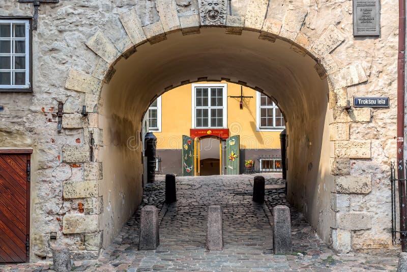 Riga Lettland - Juli, 2018: Svensk port i den gamla staden av Riga Gammal båge av den svenska porten på den Troksnu gatan i gamma arkivfoton
