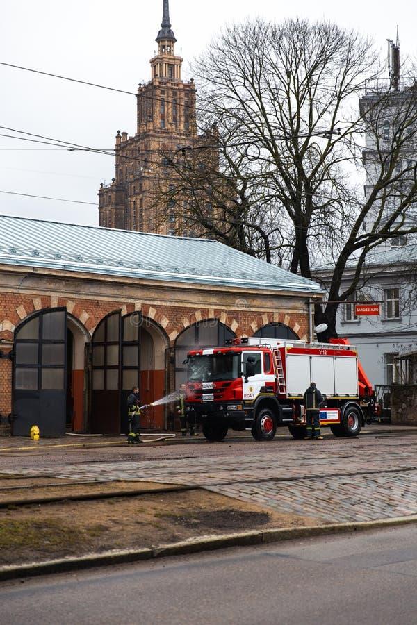 RIGA, LETTLAND - 16. MÄRZ 2019: Löschfahrzeug ist gesäuberte - Fahrer wäscht Feuerwehrmann-LKW an einem depo - szenische Ansicht stockbild