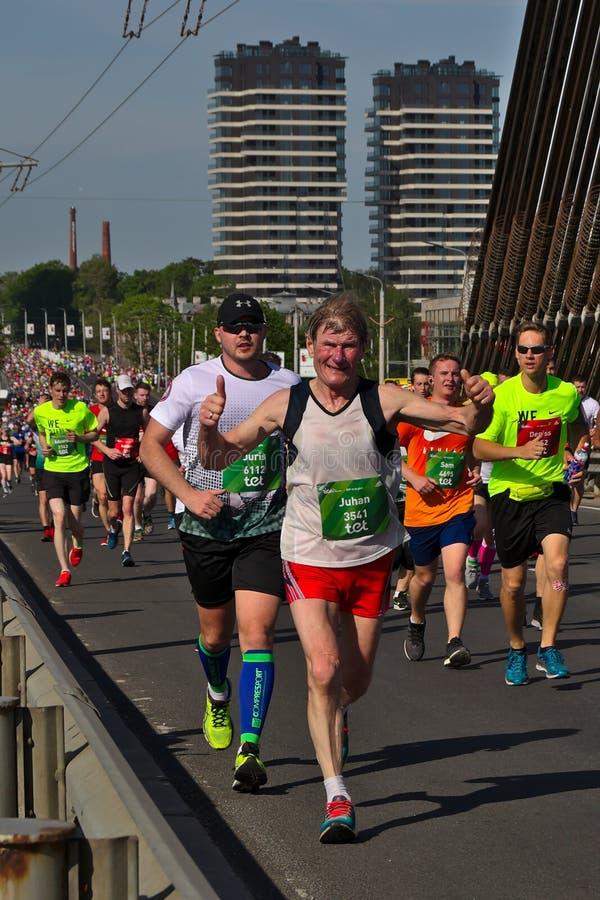Riga, Lettland - 19. Mai 2019: Älterer Marathonläufer, der tapfer eine Brücke kreuzt lizenzfreies stockbild