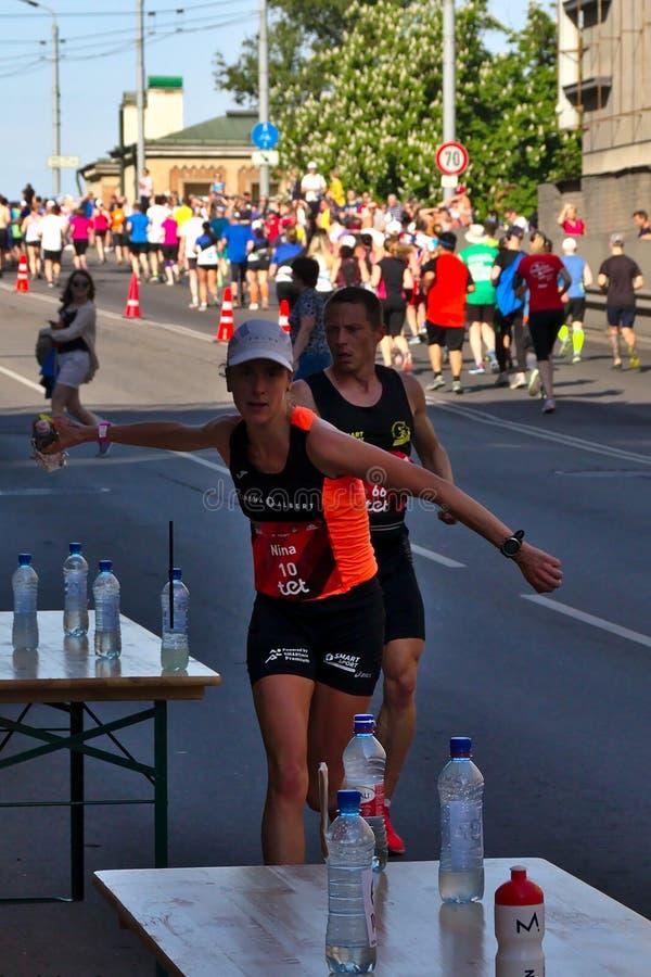 Riga, Lettland - 19. Mai 2019: Ergreifungssport des kaukasischen weiblichen Ausleseläufers trinkt mit großer Geschwindigkeit lizenzfreies stockbild