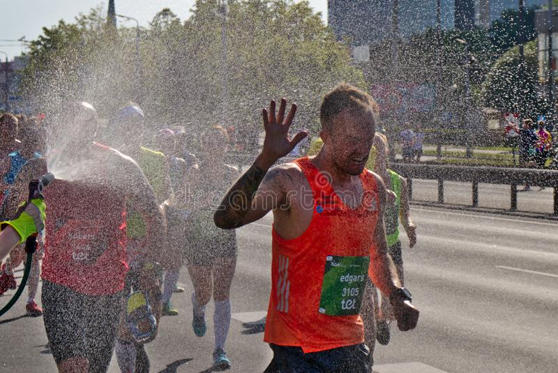 Riga, Lettland - 19. Mai 2019: Männlicher Teilnehmer des Sprays des empfangenden Wassers des Marathons zu hes Gesicht stockbild