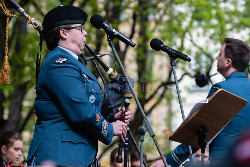 RIGA LETTLAND - MAJ 4, 2019: Den festliga konserten i staden parkerar Kanadensiska arm?musiker spelar s?ckpipa royaltyfria foton