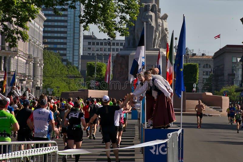 Riga Lettland - Maj 19 2019: Maratonl?pare som n?r frihetsstatyn med traditionellt bekl?dde hejaklacksledare, ger h?ga pickolafl? arkivfoton
