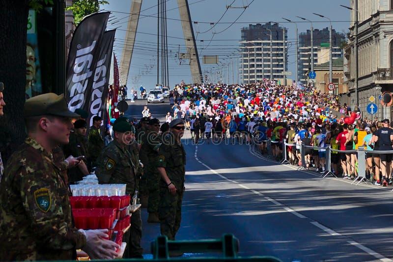 Riga Lettland - Maj 19 2019: Milit?ra volont?rer som v?ntar p? maratonl?pare royaltyfri bild
