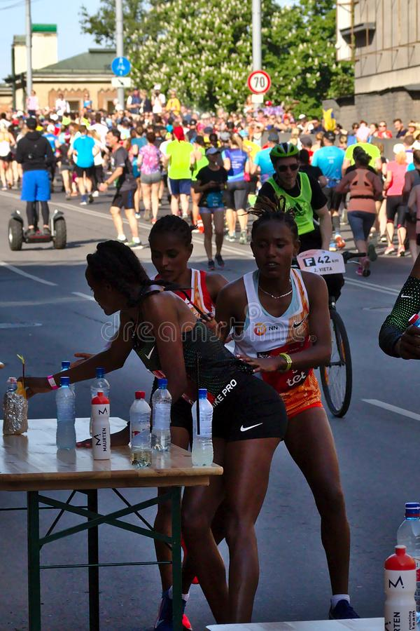 Riga Lettland - Maj 19 2019: Tre kvinnliga elitl?pare som finner deras sportar, dricker fr?n tabellen under maraton royaltyfri fotografi