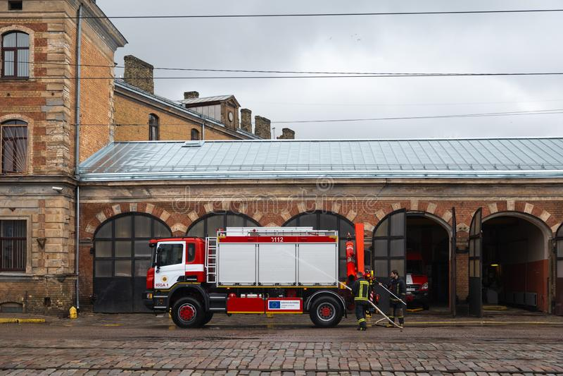 RIGA LETTLAND - MARS 16, 2019: Brandlastbilen göras ren - chauffören tvättar brandmanlastbilen på en depo arkivfoto