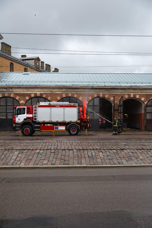 RIGA LETTLAND - MARS 16, 2019: Chauffören tvättar brandmanlastbilen på en depo bakifrån - brandlastbilen göras ren arkivfoto