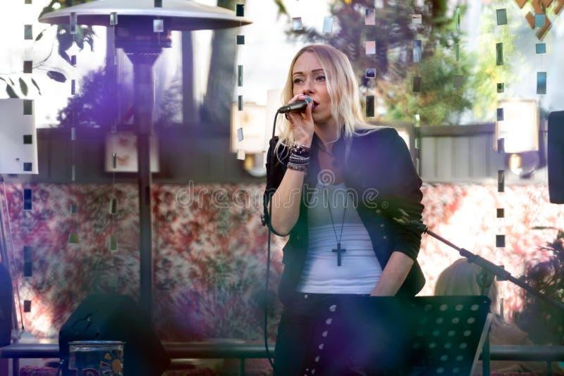 RIGA, LETTLAND - 14. SEPTEMBER 2018: Blondine singen einem Karaoke Café im Freien stockbild