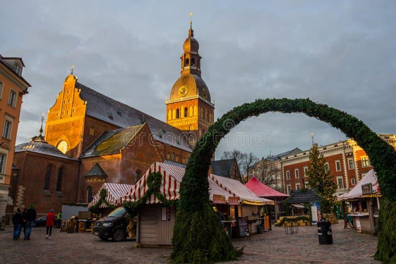 Riga, Lettonia: Il gruppo di persone non identificato gode del mercato di Natale tenuto al mercato di Natale dell'inverno Riga fotografia stock libera da diritti