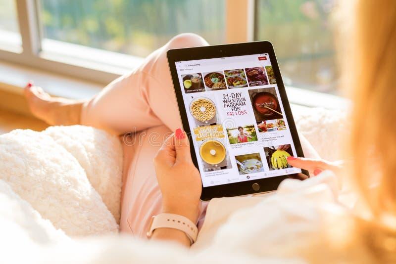 Riga, Lettonia - 21 luglio 2018: Donna che per mezzo del app di Pinterest su iPad immagine stock libera da diritti