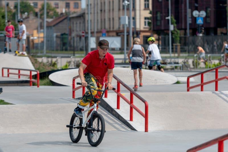 RIGA, LETTONIA - 20 LUGLIO 2018: L'adolescente nel carri dello skatepark immagini stock libere da diritti