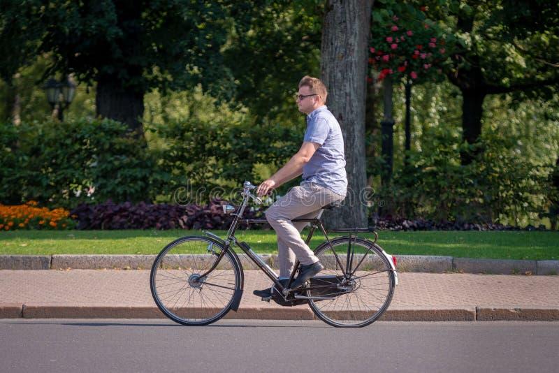 RIGA, LETTONIA - 18 LUGLIO 2018: Un uomo con una bicicletta funziona lungo la via fotografia stock libera da diritti