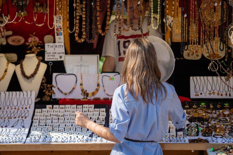 RIGA, LETTONIA - 31 LUGLIO 2018: Una donna nel chiosco del ricordo sceglie i gioielli ambrati fotografia stock libera da diritti