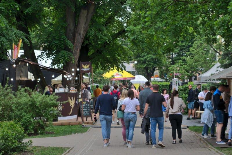 Riga, Lettonia - 24 maggio 2019: Gruppo di amici o di famiglia che camminano in vie del festival lettone della birra fotografia stock