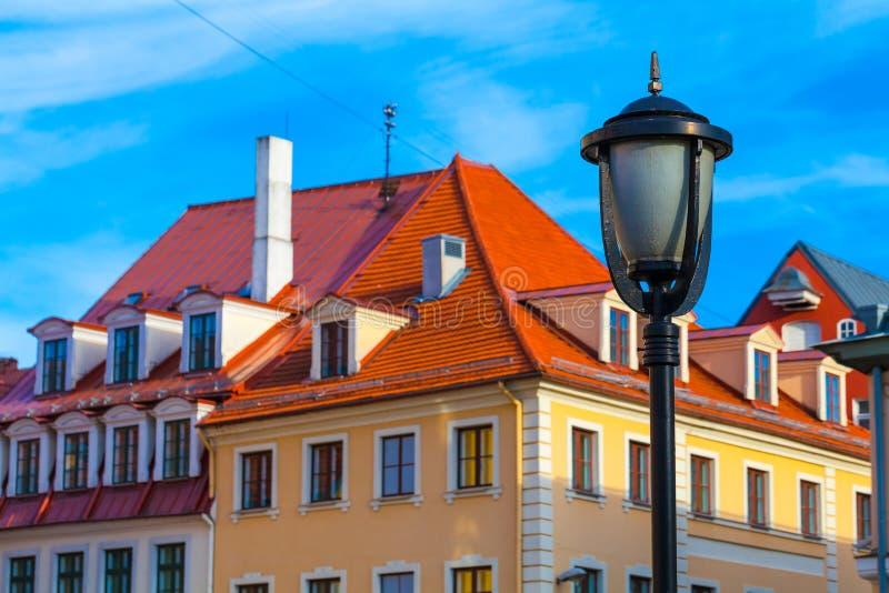 RIGA, LETTONIA - 6 MAGGIO 2017: La vista sulla lampada di via e le vecchie case di colore con il tetto piastrellato sono situate  fotografia stock