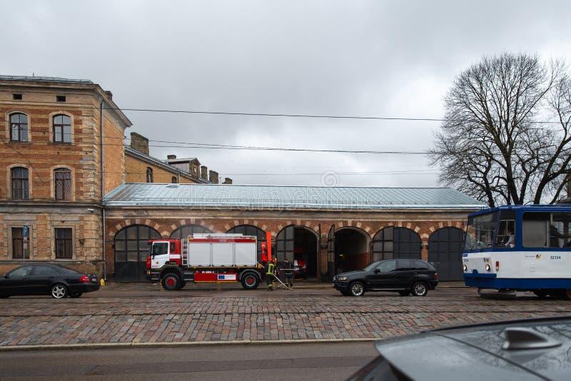 RIGA, LETTONIA - 16 MARZO 2019: Il camion dei vigili del fuoco sta pulendo - il driver lava il camion del pompiere ad un depo fotografia stock libera da diritti
