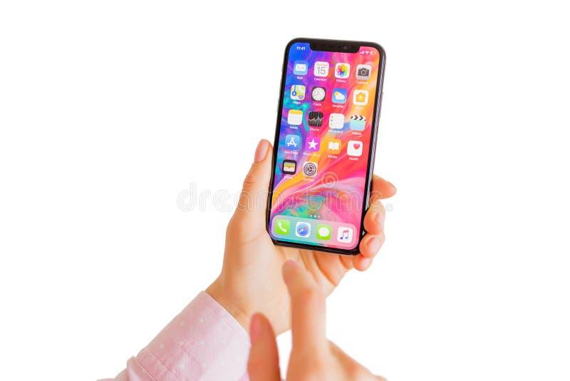 Riga, Lettonia - 15 marzo 2018: Persona che tiene a disposizione ultimo iPhone X della generazione fotografia stock libera da diritti