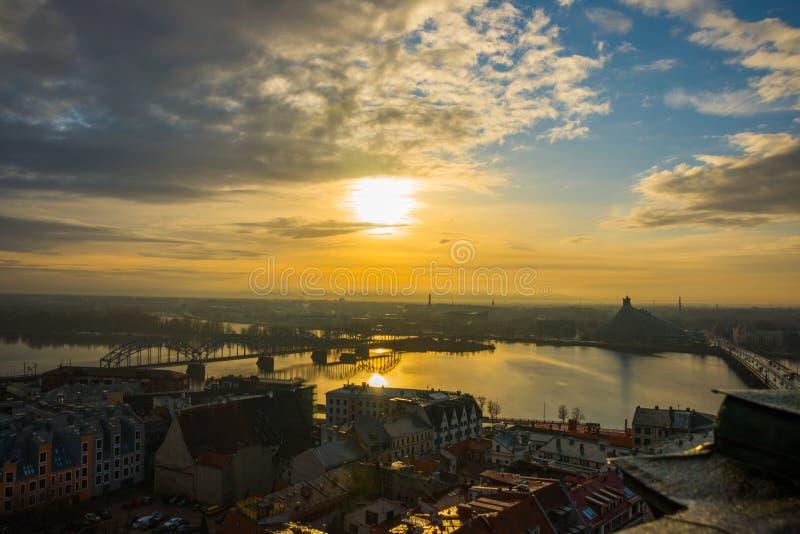Riga, Lettonia: Vista superiore della città, di un panorama del fiume e del ponte al tramonto immagine stock libera da diritti