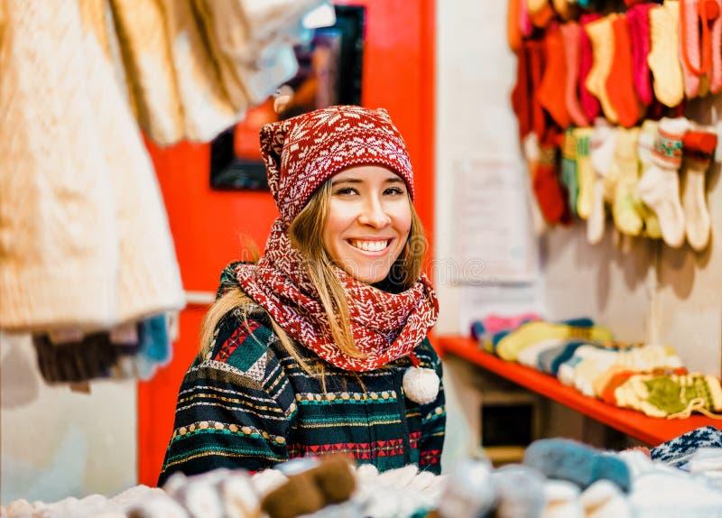 Riga, Lettonie - 24 décembre 2015 : Jeune femme de sourire décrite à une des stalles pendant le marché de Noël de l'hiver Riga de photos stock