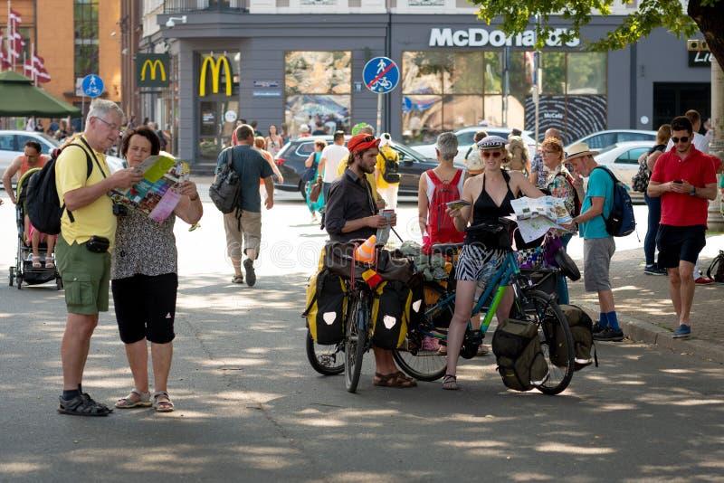 RIGA, LETTONIE - 18 JUILLET 2018 : Les touristes de vélo s'arrêtent au centre de la ville sur la rue et observent la carte image stock