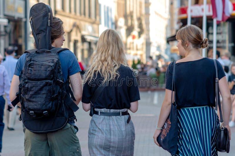 RIGA, LETTONIE - 26 JUILLET 2018 : Un homme et deux femmes marchent le long des rues de la ville Vue du dos images libres de droits