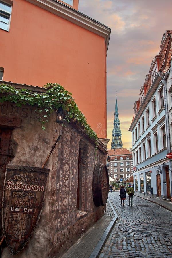 Riga, Lettonie - juillet 2017 : Vieille rue médiévale la nuit avec l'église de Peters Lutheran de saint à Riga, Lettonie photo libre de droits